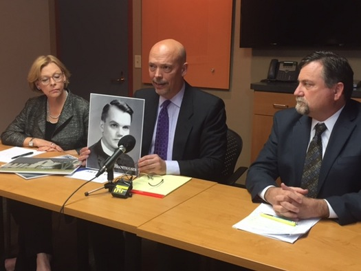 Attorneys Patrick Noaker, center, holding a portrait of the Rev. John Huchthausen, and Marci Hamilton, left, and Leander James.