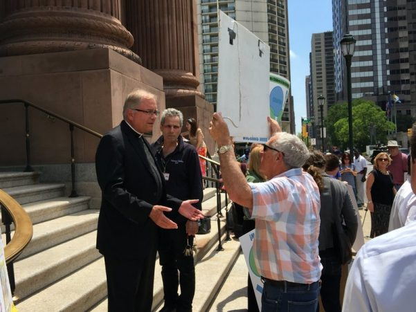 The Rev. Dennis Gill, rector and pastor of the Cathedral Basilica of Saints Peter and Paul, speaks to a protester before Monday afternoon's event got underway.
