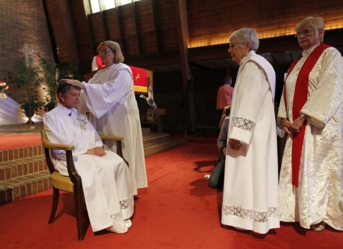Rosemarie Smead weeps openly as almost entire congregation comes to lay their hands on her head in blessing, as she was ordained Roman Catholic priest during Celebration of Ordination in Louisville