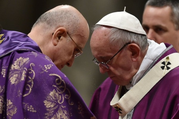 Pope Francis (R) puts ashes on the head of Cardinal Bertone during the Ash Wednesday mass opening Lent, the forty-day period of abstinence and deprivation for Christians, before Holy Week and Easter, on February 10, 2016 in Vatican.