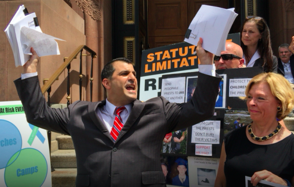 State Rep. Mark Rozzi holds up copies of clergy sex-scandal grand-jury reports before throwing them on the steps of the Cathedral Basilica of Saints Peter and Paul during Monday afternoon's protest.