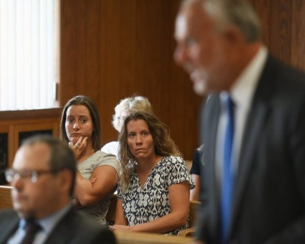 ate Drumgoole, center, and her wife, Jaclyn Vanore, rear left, during a court hearing. Drumgoole is suing Paramus Catholic High School, alleging it violated the state's discrimination law when she was fired because she's married to a woman.